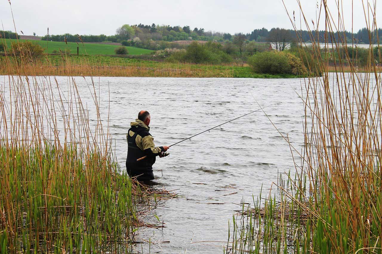 Angler mit Wathose im Wasser