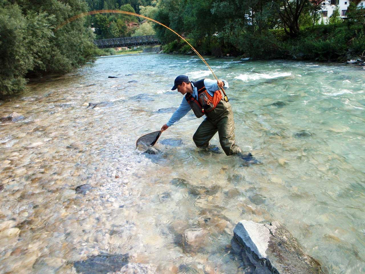 Angler mit Wathose und Kescher