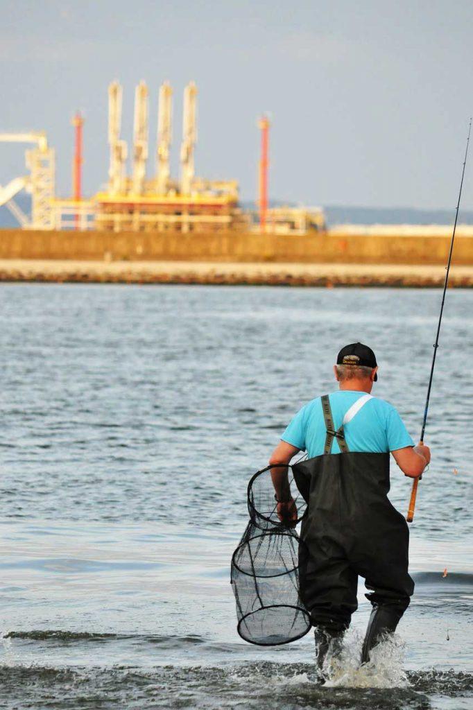 Angler mit Wathose und Reuse