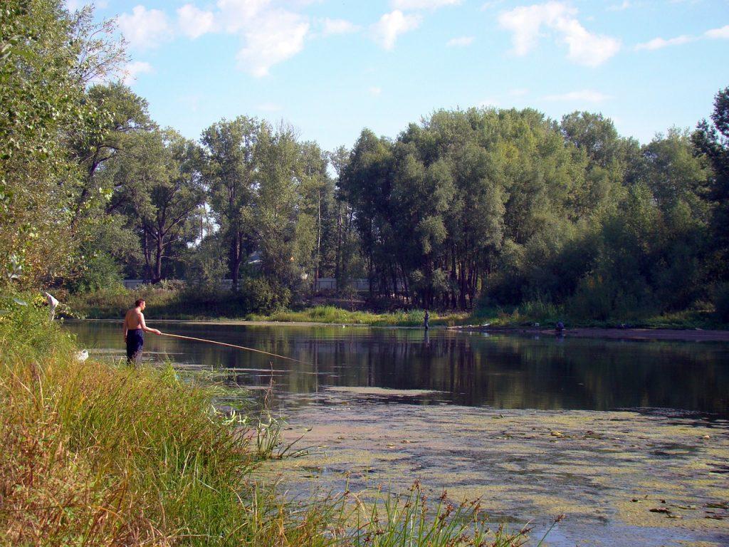Fischer beim Wels angeln mit Wels Angel vom Ufer